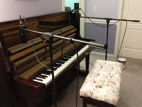 Photo of piano recording setup with boom mics